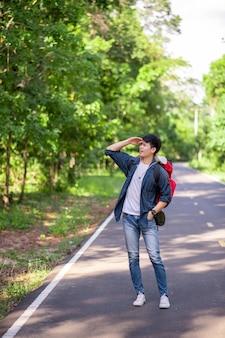Ritratto allegro giovane con zaino in piedi e sorridente nel sentiero nel bosco, copia spazio