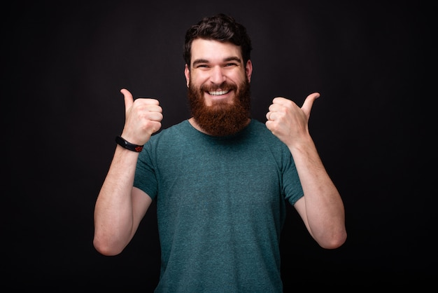 Portrait of cheerful young man with beard showing thumbs up while standing over dark background