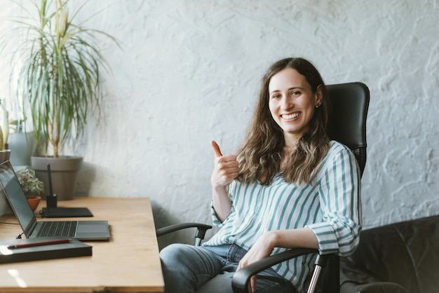 Portrait of cheerful young office wonan sitting in front of desk and showing thumbs up