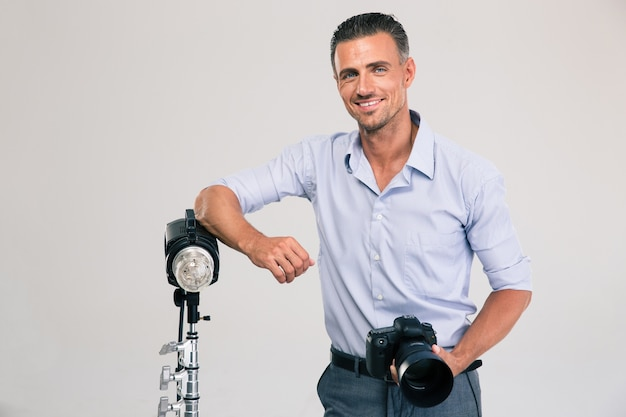 Portrait of a cheerful young photographer standing with camera isolated