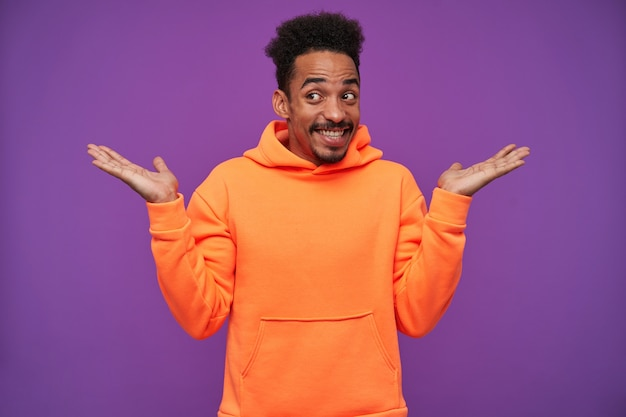 Portrait of cheerful young pretty bearded dark skinned man with black curly hair shrugging with raised palms and smiling broadly, dressed in orange hoodie while posing on purple