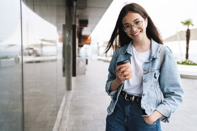 Portrait of a cheerful young pretty woman student wearing eyeglasses walking outdoors resting listening music with earphones drinking coffee.