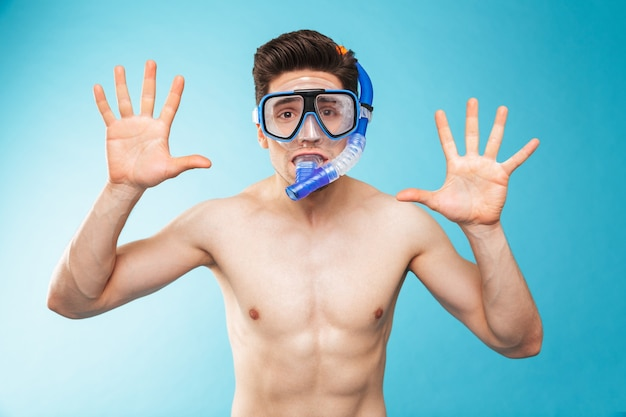 Portrait of a cheerful young shirtless man in swim goggles
