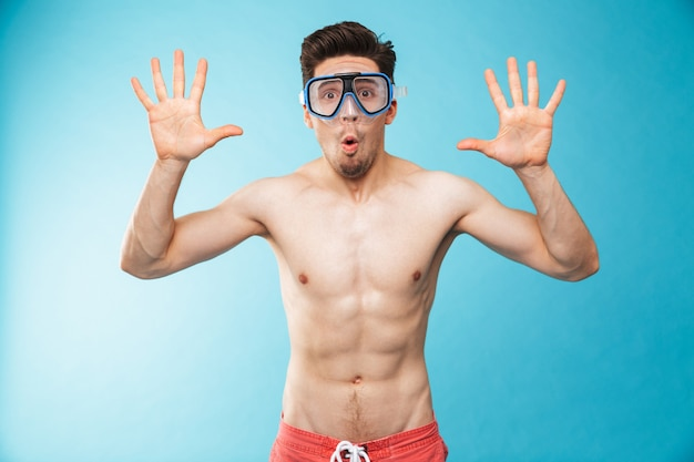Portrait of a cheerful young shirtless man in swim mask