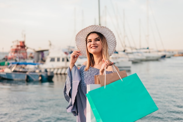 Portrait of a cheerful young shopaholic woman in a hat and dress on a background of the sea. .