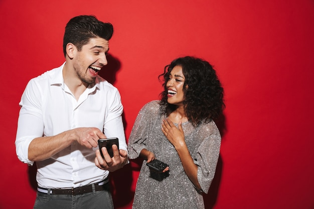 Portrait of a cheerful young smartly dressed couple standing isolated over red space, holding mobile phones