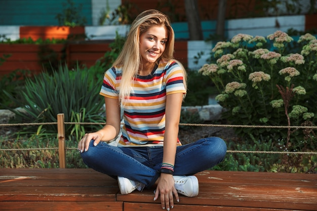 Portrait of a cheerful young teenage girl sitting on a bench