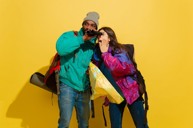 Portrait of a cheerful young tourist couple with bags isolated on yellow studio wall