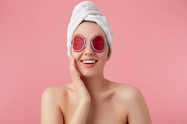 Portrait of cheerful young woman after spa with a towel on her head, with mask for eyes, broadly smiles, feels so happy, stands.