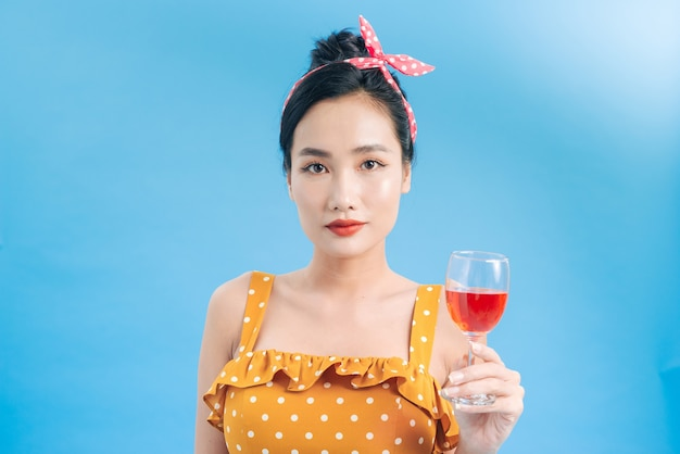 Portrait of a cheerful young woman in dress holding glass of champagne isolated over blue
