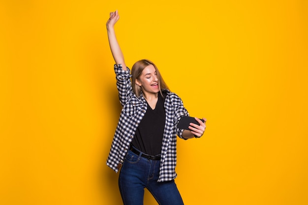 Portrait of a cheerful young woman holding mobile phone, celebrating standing isolated over yellow wall