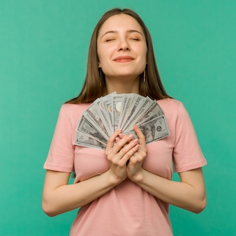 Portrait of a cheerful young woman holding money banknotes and celebrating isolated on blue background