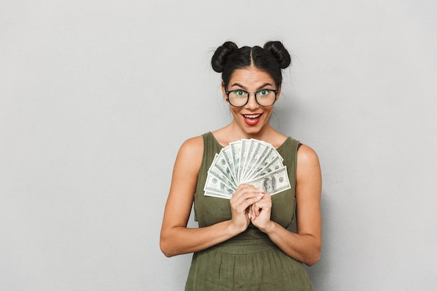 Portrait of a cheerful young woman isolated, showing money banknotes