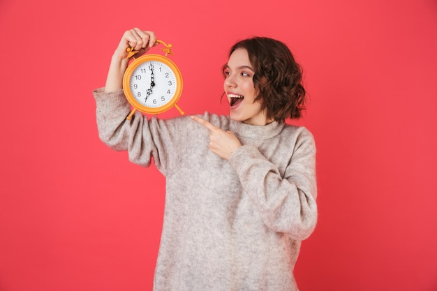Portrait of a cheerful young woman standing isolated over pink, holding alarm clock