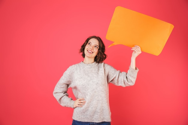 Portrait of a cheerful young woman standing isolated over pink, holding empty speech bubble