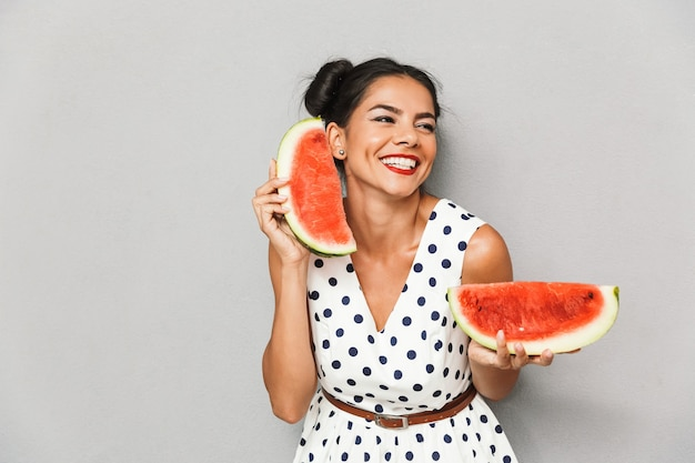 Portrait of a cheerful young woman in summer dress isolated, holding watermelon slice