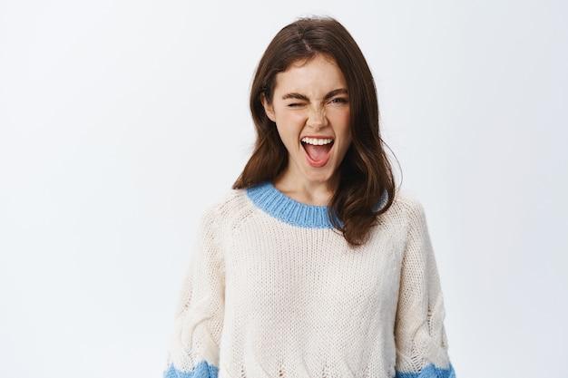 Ritratto di giovane donna allegra in maglione che mostra la lingua e strizza l'occhio eccitata, godendo la festa, esprime divertimento ed emozioni positive, in piedi contro il muro bianco