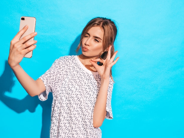Portrait of cheerful young woman taking photo selfie. beautiful girl holding smartphone camera. smiling model posing near blue wall in studio. shows ok sign.winks and makes duck face