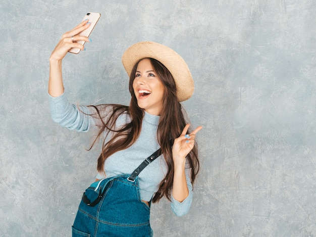 Portrait of cheerful young woman taking photo selfie and wearing modern clothes and hat.  . shows peace sign