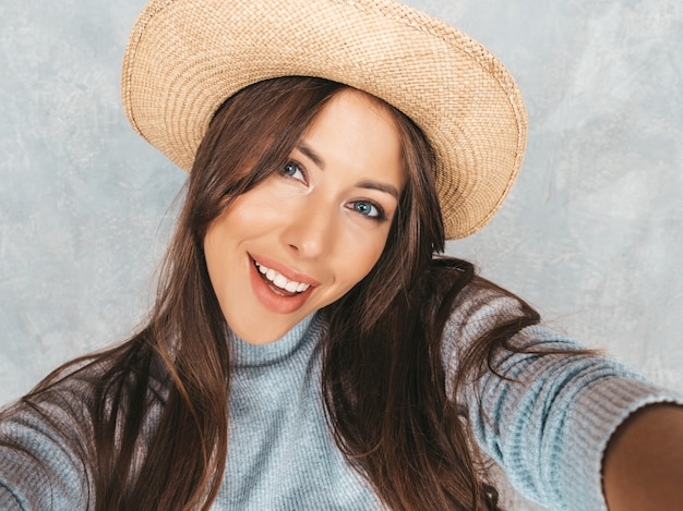 Portrait of cheerful young woman taking photo selfie and wearing modern clothes and hat.