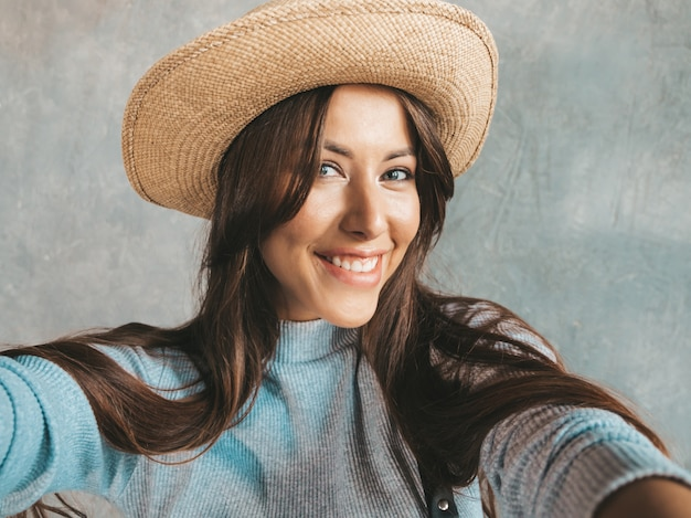 Portrait of cheerful young woman taking photo selfie with inspiration and wearing modern clothes and hat.