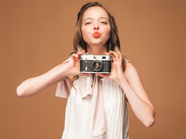 Portrait of cheerful young woman taking photo with inspiration and wearing white dress. girl holding retro camera. model posing. giving kiss