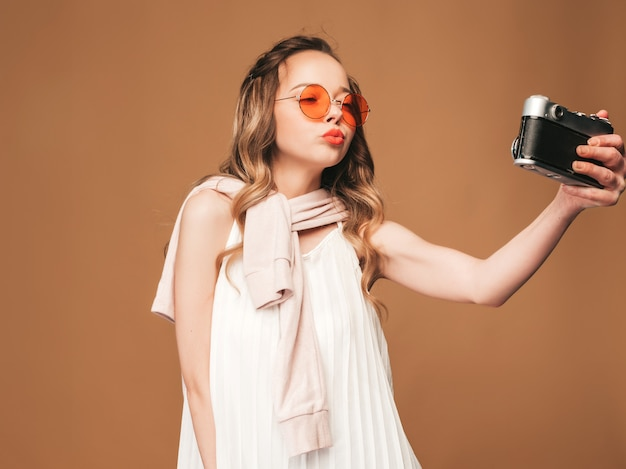 Portrait of cheerful young woman taking photo with inspiration and wearing white dress. girl holding retro camera. model posing.making selfie