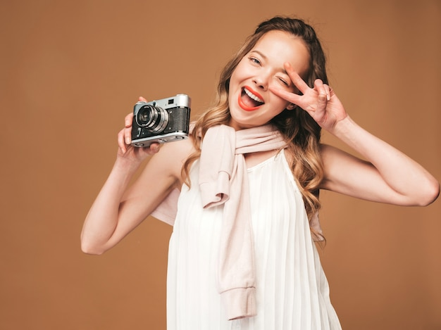 Portrait of cheerful young woman taking photo with inspiration and wearing white dress. girl holding retro camera. model posing