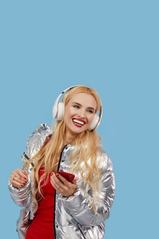 Portrait of cheerful young woman wearing casual silver jacket isolated, listening to music with headphones, dancing. wow and surprised face