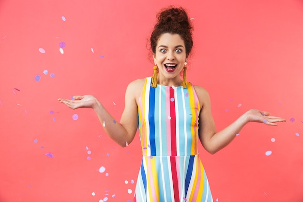 Portrait of a cheerful young woman wearing dress standing isolated over red background