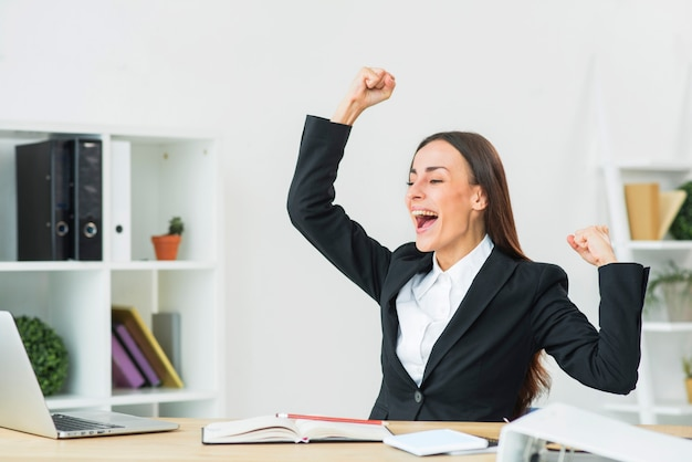 Portrait of cheering young businesswoman clenching her fist