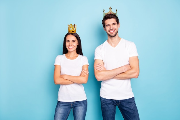 Portrait of cheery content couple wearing tiara folded arms isolated