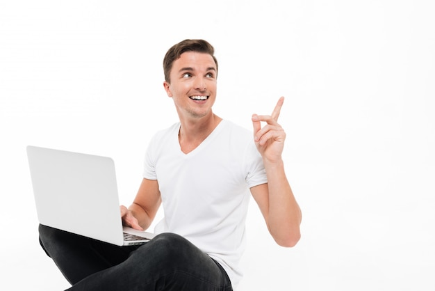 Portrait of a cheery handsome man holding laptop computer