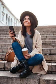 Portrait of a cheery smiling woman texting on mobile phone