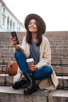 Ritratto di una donna sorridente allegra che manda un sms sul telefono cellulare