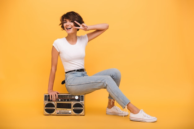 Portrait of a cheery young woman sitting record player