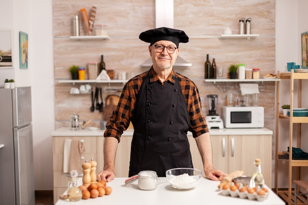 Portrait of chef wearing bonete looking at camera and smiling. retired elderly baker in kitchen uniform preparing pastry ingredients on wooden table ready to cook homemade tasty bread, cakes and pasta