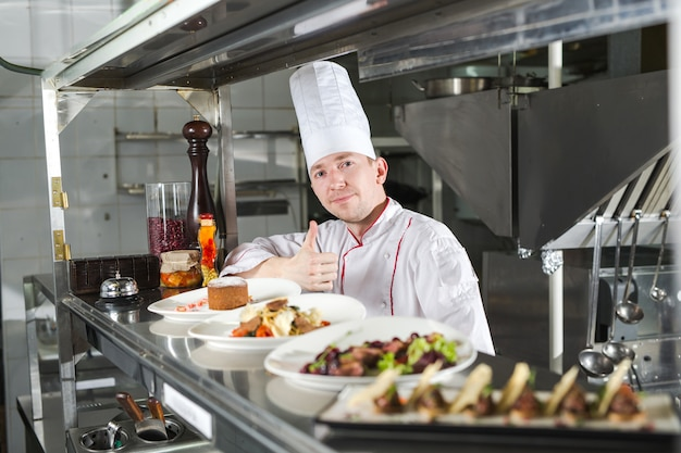 Portrait of a chef with cooked food in the kitchen in the restaurant.