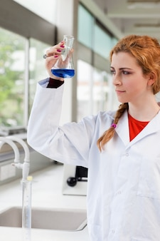 Portrait of a chemist looking at a blue liquid