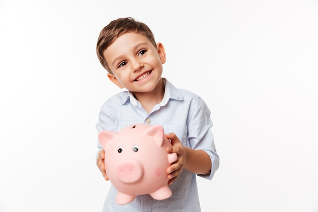 Portrait of a cherry cute little kid holding piggy bank