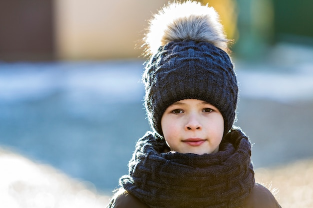 Portrait of child boy in hat and scarf outdoors in sunny winter day