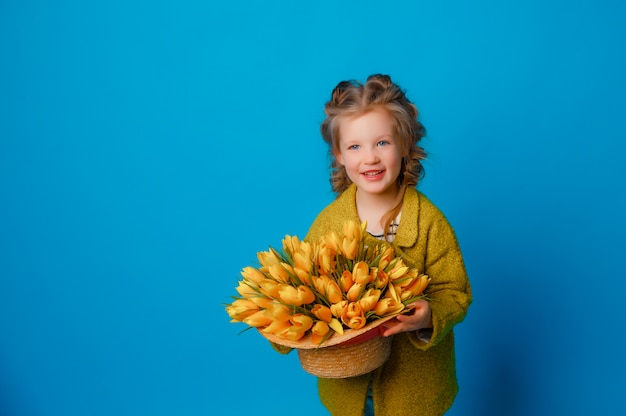 Portrait of a child a girl in rain boots a bouquet of spring flowers tulips on a colored blue space