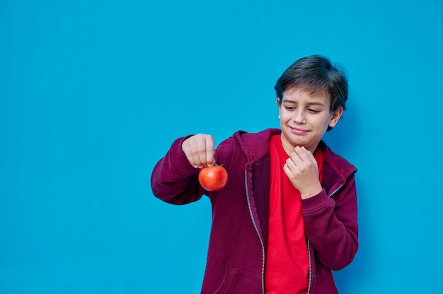A portrait of child holds a tomato and looks at it with a rejection face. copy space
