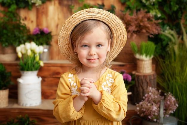 祈る肖像画の子。小さな女の子の手祈り、手を組んで信仰、精神性、宗教の祈りの概念。黄色のドレスと庭、夏の麦わら帽子でかわいい小さなブロンドの女の子。