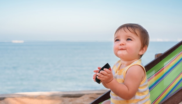 Portrait of a child at sea. baby on sun lounger eating watermelon