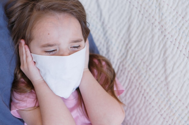 Portrait of a child who covered her face with a mask.