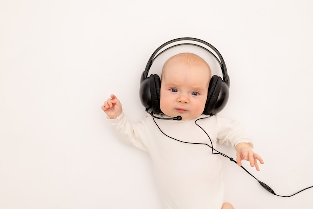 Portrait of a child with headphones. stay home, coronavirus 19. baby 6 months listening to music.
