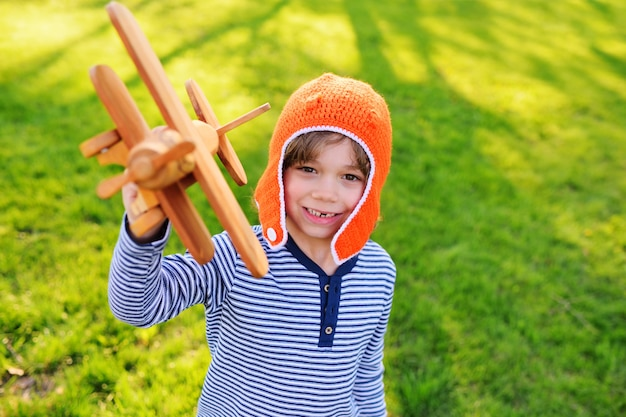 Portrait of a child with a toy airplane in hands against a background of greenery.