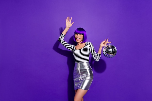 Portrait  of childish person with eyeglasses eyewear moving screaming holding mirror ball isolated over purple violet background