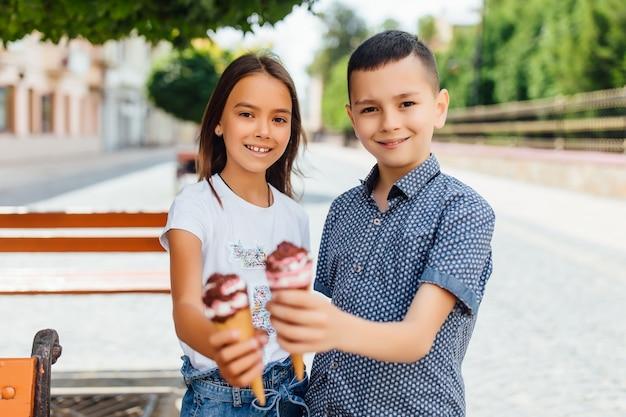 Ritratto di bambini, fratello e sorella in panchina a mangiare un gelato dolce.